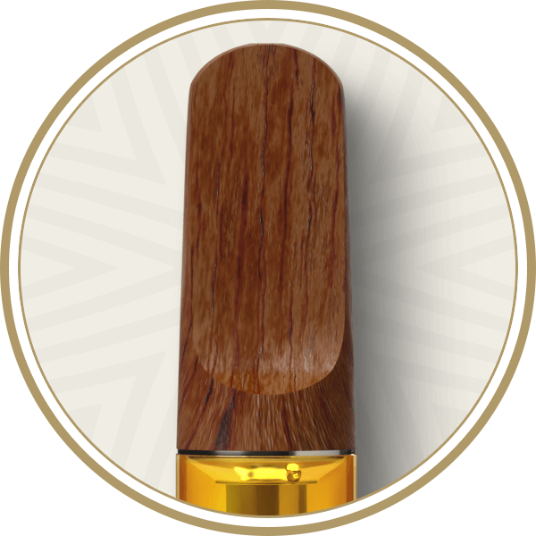 Close up of sandalwood mouthpiece and golden extra virgin cannabis oil